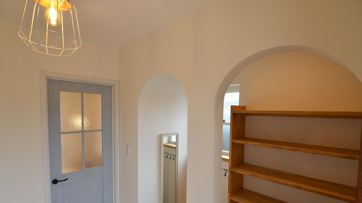 自然素材の漆喰と極厚幅広フローリングのかわいい家 玄関のWアーチ